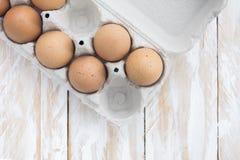 Ägg i ett magasin och en träbakgrund, bästa sikt Fotografering för Bildbyråer