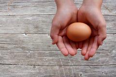 Ägg i händer på träbakgrund royaltyfri foto