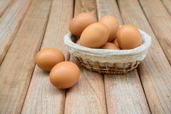 Ägg i korg på träbakgrund Royaltyfria Foton