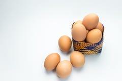 Ägg i korg på vit bakgrund Arkivfoto