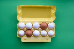 Ägg i låda på den gröna bakgrunden arkivfoton