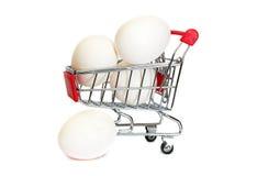 Ägg i shoppingvagnen isolaten i vit Fotografering för Bildbyråer