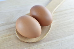 Ägg i träsked på träbakgrund Arkivfoto