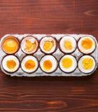 Ägg i varierande grader av tillgänglighet beroende av tiden av kokande ägg Fotografering för Bildbyråer