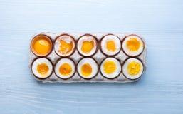 Ägg i varierande grader av tillgänglighet beroende av tiden av kokande ägg Arkivfoto