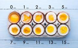 Ägg i varierande grader av tillgänglighet beroende av tiden av kokande ägg Arkivfoton