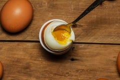 Ägg kokade på en trätabell med en sked Kokt ägg med en sked på tabellen Ägg Royaltyfri Foto