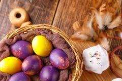 Ägg målade till påsken i guling, och lilan färgar och en muffin i sockerisläggning på ett bräde som dekoreras med fjädrar Royaltyfri Bild