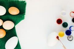 Ägg, målarfärg och målarfärgborste på tabellen bakgrundsbröd bakar ihop white för skuggor för förberedelse för easter äggbakelser Arkivbilder