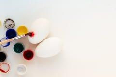 Ägg, målarfärg och målarfärgborste på tabellen bakgrundsbröd bakar ihop white för skuggor för förberedelse för easter äggbakelser Fotografering för Bildbyråer