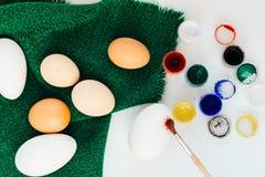 Ägg, målarfärg och målarfärgborste på tabellen bakgrundsbröd bakar ihop white för skuggor för förberedelse för easter äggbakelser Royaltyfria Foton