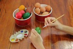 Ägg målas av händer av den unga kristna mannen med paintbrust förbereder sig för easter tid Arkivbild