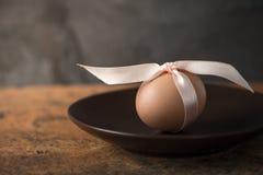 Ägg med bandet på den bruna plattan Arkivbild