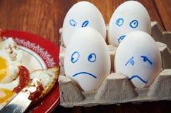 Ägg med den förskräckta framsidan och det stekte ägget arkivbild