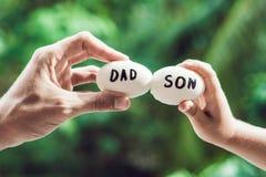 Ägg med inskrifter fader och son Problem between avlar a Arkivbild