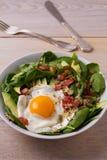 Ägg med quinoa-, avokado-, bacon-, spenat- och pumpafrö i den vita bunken Royaltyfri Bild