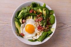 Ägg med quinoa-, avokado-, bacon-, spenat- och pumpafrö i den vita bunken Arkivfoto