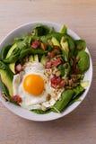 Ägg med quinoa-, avokado-, bacon-, spenat- och pumpafrö i den vita bunken Fotografering för Bildbyråer