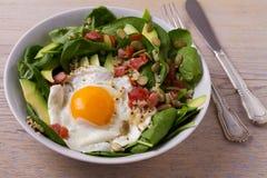 Ägg med quinoa-, avokado-, bacon-, spenat- och pumpafrö i den vita bunken Royaltyfria Bilder