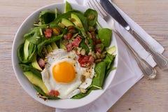 Ägg med quinoa-, avokado-, bacon-, spenat- och pumpafrö i den vita bunken Arkivbild