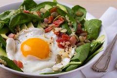 Ägg med quinoa-, avokado-, bacon-, spenat- och pumpafrö i den vita bunken Royaltyfria Foton