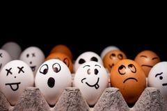 Ägg med roliga uttryck som simulerar mänskliga framsidor Begrepp av etnisk mångfald och lynnen arkivbild