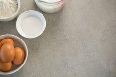 Ägg med socker och mjöl i bunkar Arkivbild