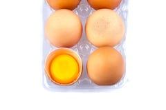 Ägg och äggula i en plast- genomskinlig packe Arkivfoto
