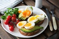 Ägg och avokado, grön sallad och körsbärsröda tomater på den vita plattan sund frukost Fotografering för Bildbyråer