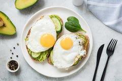Ägg- och avokadofrukostrostat bröd på den vita plattan Royaltyfria Foton