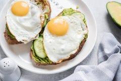 Ägg- och avokadofrukostrostat bröd på den vita plattan Fotografering för Bildbyråer