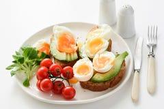 Ägg- och avokadorostade bröd på den vita plattan, closeupsikt Royaltyfri Foto
