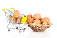 Ägg och bakgrund för vit för shoppingtrollyisolatedon Arkivbilder