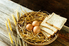 Ägg och bröd i korgen Arkivfoto