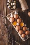 Ägg och brutna ägg och vaktelägg i packen på en träbakgrund Lantlig stil Ägg Påskfotobegrepp Arkivfoton