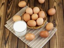 Ägg och ett exponeringsglas av mjölkar Arkivbild