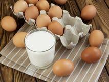 Ägg och ett exponeringsglas av mjölkar Arkivbilder
