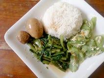 Ägg och griskött i grodor för brun sås, uppståndelse Fried Swamp Cabbage och uppståndelse stekte zucchinin med ägget med ris thai Arkivbilder