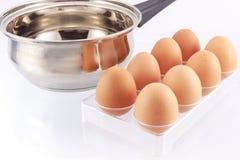 Ägg och kitchenware på vit bakgrund Arkivbild