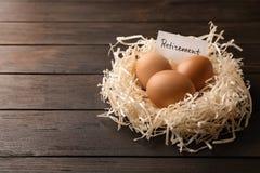 Ägg och kort med ordet AVGÅNG i rede på träbakgrund, utrymme för text royaltyfri foto