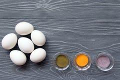Ägg och målarfärger för vit fega på en grå tabell Fira Easte Arkivfoton