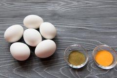 Ägg och målarfärger för vit fega på en grå tabell Fira Easte Royaltyfria Bilder