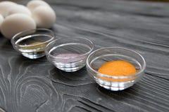 Ägg och målarfärger för vit fega på en grå tabell Fira Easte Fotografering för Bildbyråer