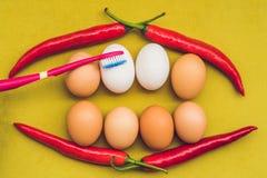Ägg och röd peppar i form av en mun med tänder Vita ägg är blekte tänder Gula ägg - innan att bleka Tänder gör vit Royaltyfri Bild
