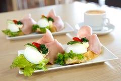 Ägg och skinksmörgåsar för traditionell europé öppet på den vita ceramien Royaltyfri Bild