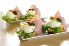Ägg och skinksmörgåsar för traditionell europé öppet på den vita ceramien Royaltyfri Foto
