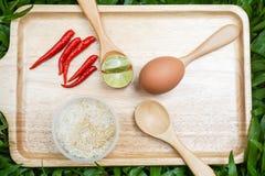 Ägg och skivad limefrukt på skeden med den röda chili och ris Arkivbild