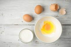 Ägg och yoghurt på den vita träbästa sikten för tabell royaltyfria bilder