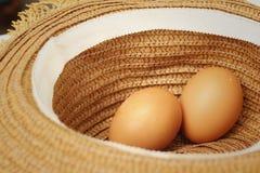 Ägg på en bakgrund av den bruna hatten Arkivfoto