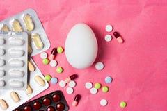 Ägg på en medicinsk bakgrund av piller och mediciner i packar royaltyfri foto